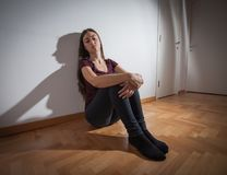 Depressed young woman. Sad young woman , depressed female , emotional problems, sitting on floor at empty room Royalty Free Stock Photography