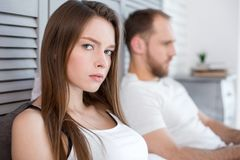 Sad young woman feeling lonely. So lonely. Attractive unsmiling long-haired young women feeling lonely and her men being next to her and paying no attention to Stock Image