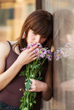 Sad young woman with a flowers Stock Image