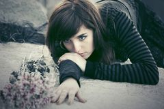 Sad young woman with a flowers lying on tombstone. Outdoor Royalty Free Stock Photo