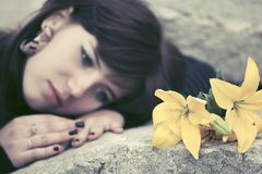 Sad young woman with a flowers lying on tombstone Stock Photo