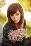 Sad young woman with a flowers Stock Photo