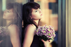 Sad young woman with a flowers standing at the wall Stock Photo