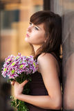 Sad young fashion woman with a flowers at the wall Stock Photography