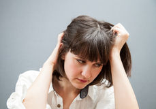 Sad young woman. Grey background Royalty Free Stock Photo