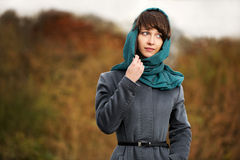 Sad young fashion woman in grey classic coat walking outdoor royalty free stock images