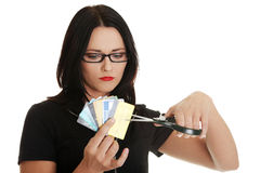Sad young woman has to destroy her credit cards. Sad young woman has to destroy her credit card against a white background stock photos