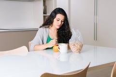 Sad young woman having breakfast stock photos