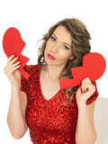 Sad Young Woman Holding a Broken Valentines Heart Royalty Free Stock Photography