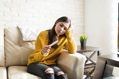 Woman Feeling Sad For Unexpected Pregnancy. Sad young woman holding pregnancy test kit on sofa at home royalty free stock photo