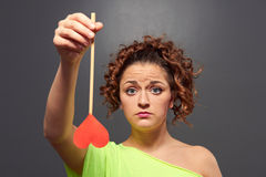 Sad young woman holding red heart Stock Images
