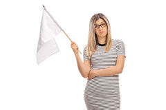Sad young woman holding a white flag. Isolated on white background Royalty Free Stock Images