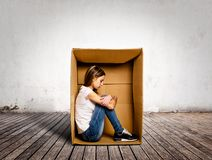 Sad young woman inside a Box. On a room royalty free stock image