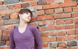 Sad young woman leaning against wall Stock Photography