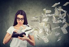 Sad woman looking at her wallet with money dollar banknotes flying out away royalty free stock photography