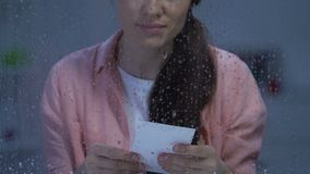 Sad young woman looking at photo near rainy window, missing child after divorce. Stock footage stock footage