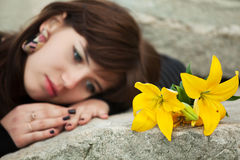 Sad young woman lying on the tombstone. Young woman with a flowers lying on the tombstone Royalty Free Stock Photos