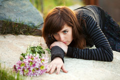 Sad young woman lying on the tombstone Royalty Free Stock Photography