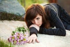 Sad young woman lying on the tombstone. Sad young woman with a flowers lying on the tombstone Royalty Free Stock Photography