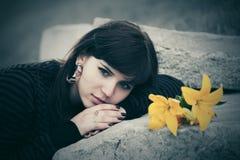 Sad young woman lying on tombstone. Sad young woman with a flowers lying on tombstone Stock Photo