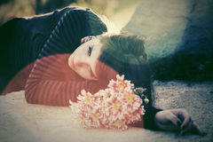 Sad young woman lying on tombstone Royalty Free Stock Photo