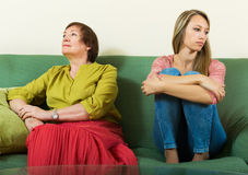 Sad young woman and  mature mother after conflict Stock Image