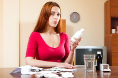 Sad young woman with medications at living room behind table Royalty Free Stock Image