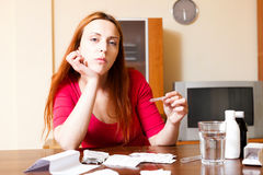 Sad young woman with medications at living room Stock Photo