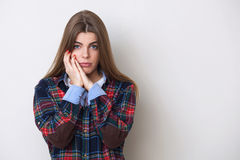 Sad young woman in plaid shirt posing against wall. Stock Photo