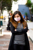 Sad young woman with protective mask feeling bad on the street in the city with air pollution, city background Stock Image