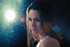Sad young woman in the rain. On black background Royalty Free Stock Images