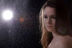 Sad young woman in the rain. On black background Stock Photo