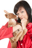 Sad young woman in red pyjama with toy Royalty Free Stock Images