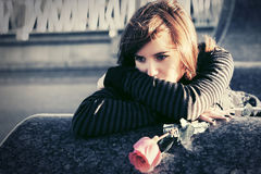 Sad young woman with a red rose in city street. Sad young fashion woman with a red rose in city street Stock Images