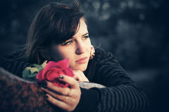 Sad young woman with a red rose. Outdoor Royalty Free Stock Images