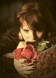 Sad young woman with a red rose outdoor Royalty Free Stock Photography
