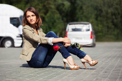 Sad young woman with red rose sitting on the road Stock Image