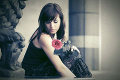 Sad young woman with a red rose sitting on tombstone. Sad young woman with a red rose sitting on the tombstone Royalty Free Stock Images