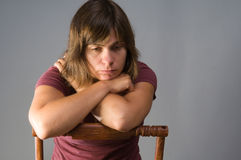 Sad young woman. Young woman, 20s, sits in chair, looking sad and lonely Royalty Free Stock Photography