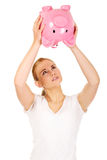 Sad young woman shaking piggybank for coins Royalty Free Stock Photography