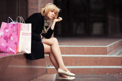 Sad young woman with shopping bags Stock Image