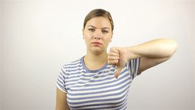 Sad young woman showing thumbs down. On white Background stock video footage