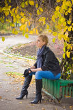 Sad young woman sit. Near autumn tree Stock Photo