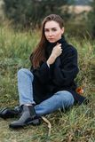 Sad young woman sitting alone on grass outdoors. Hope. Sadness. Loneliness. Autumn weather.  Stock Photography