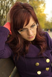 Sad young woman sitting on a bench in the park Stock Photos