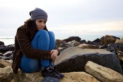 Sad young woman sitting in front of the ocean Stock Photography