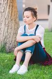 sad young woman sitting on green lawn stock photos