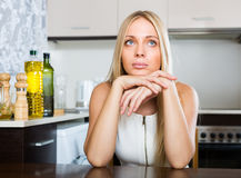 Sad young woman sitting at kitchen Stock Image