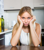 Sad young woman sitting at kitchen Royalty Free Stock Images