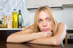 Sad young woman sitting at kitchen Royalty Free Stock Image